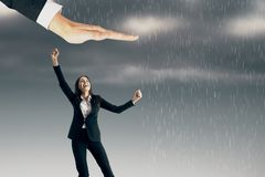 Protection and safety concept. Businessman hand over celebrating young businesswoman on rainy dull sky background. Protection and safety concept royalty free stock photos