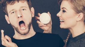 Woman applying cream to her man face. Protection and skincare. Stubborn girlfriend trying to apply cream on her boyfriend face. Man in uncomfortable situation Stock Image