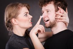 Woman applying cream to her man face. Protection and skincare. Stubborn girlfriend trying to apply cream on her boyfriend face. Man in uncomfortable situation Royalty Free Stock Photography