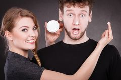 Woman applying cream to her man face. Protection and skincare. Stubborn girlfriend trying to apply cream on her boyfriend face. Man in uncomfortable situation Stock Photo