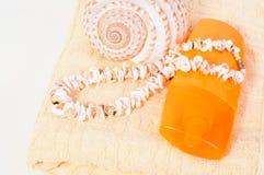 Protection solaire de bouteille de jet, serviette, coquilles Photographie stock