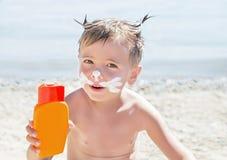 Protection solaire de dessin de chat de moustaches et x28 ; lotion& x29 de bronzage ; sur le visage de garçon de hippie avant le  Images stock