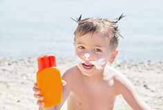 Protection solaire de dessin de chat de moustaches et x28 ; lotion& x29 de bronzage ; sur le visage de garçon de hippie avant le  Photo libre de droits