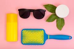 Protection solaire, peigne, crème sur un fond rose photographie stock libre de droits