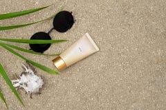 Protection solaire, verres, coquille, palmette sur le sable images libres de droits