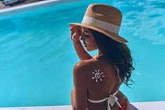 Protection from sun. Rear view of young woman with a drawn sun on her shoulder sunbathing while sitting by the pool outdoors Royalty Free Stock Images