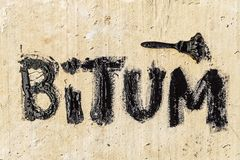 Protective bitumen mastic on concrete pavement with a brush. Bitum - black bituminous word. Construction concept royalty free stock image