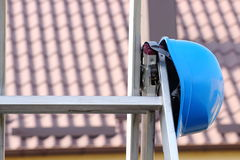 Protective blue helmet on aluminum ladder, safety at work Stock Photo