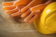 Protective building helmet electricians gloves on wood board Stock Images