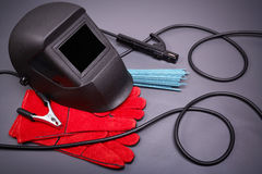 Protective clothing and accessories welder. Welding equipment, welding mask, protective leather gloves, welding electrodes, high-voltage wires with clips, set of Royalty Free Stock Image