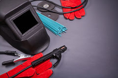 Protective clothing for welding. Welding equipment, welding mask, protective leather gloves, welding electrodes, high-voltage wires with clamps, cutting disc for Stock Images