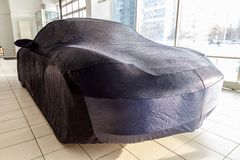 Protective cover awning for cars, blue, made of special fabric, custom-made at the auto repair shop, covering an expensive sports. Car, prepared for winter royalty free stock photos