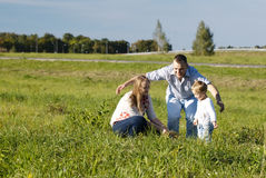 Protective father playing with his wife and son. In a grassy field in open countryside as they laugh and frolic enjoying the fresh air and sunshine Royalty Free Stock Image