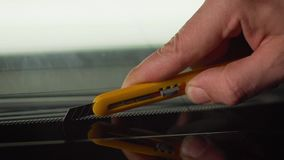 Car wrapping specialists straightening vinyl foil or film to remove ari bubbles cut carbon film. The protective film is removed fr. The protective film is stock video footage
