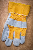 Protective glove on wooden board Stock Photos
