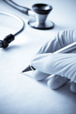 Protective Gloved Hand in Medical Scene Writing Stock Photo