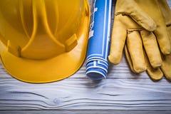 Protective gloves building helmet blue blueprints on wooden boar Stock Images