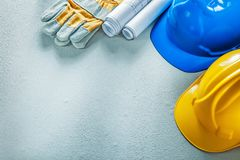 Protective gloves building helmets blueprints on concrete backgr. Ound royalty free stock photo