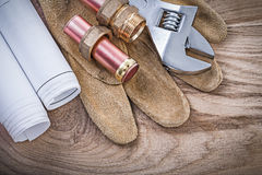 Protective gloves copper water pipe blueprints hose nipples adju. Stable wrench on wooden board plumbing concept Royalty Free Stock Photos
