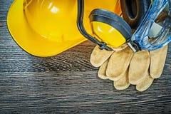 Protective gloves glasses earmuffs building helmet on wooden boa Stock Photo