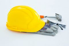 Protective gloves with hammer, glasses and yellow hard hat Stock Image