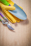 Protective gloves hand shovel secateurs on wooden board gardenin Royalty Free Stock Photo