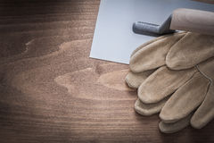 Protective gloves and plastering trowel construction concept Stock Images