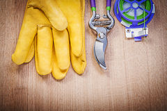 Protective gloves secateurs garden tie wire on wooden board gard Royalty Free Stock Image