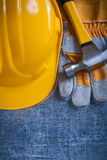 Protective gloves yellow building helmet and metal Royalty Free Stock Photos