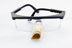 Protective goggles and fifty euro banknote Stock Images