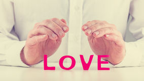 Protective hands over word Love Royalty Free Stock Images