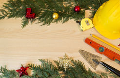 Protective helmet, mason tools  and Christmas decorations on wooden background Royalty Free Stock Photo