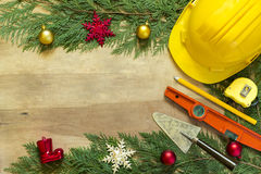 Protective helmet, mason tools and Christmas decorations on wooden background.  royalty free stock photo