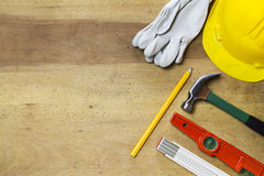 Protective helmet, mason tools and project drawings on wood background Royalty Free Stock Images