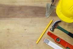 Protective helmet, mason tools  on wood background Stock Images