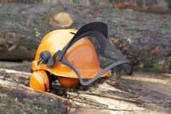 Protective helmet outdoor shot. Orange protective helmet with ear- and face- protection.  Outdoor shot in woody ambiance Stock Photos