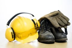 Protective helmet and work boots on a wooden table. Safety and h. Ealth protection accessories for construction workers. White isolated background royalty free stock images