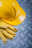 Protective leather gloves building helmet on fluted metal sheet Royalty Free Stock Images
