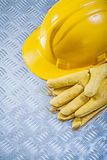 Protective leather gloves hard hat on channeled metal sheet cons Royalty Free Stock Photography