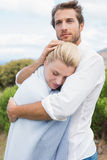 Protective man hugging his girlfriend in blue blanket outside Stock Photography