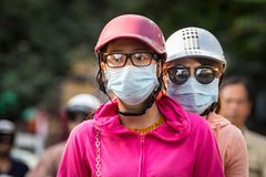Unrecognizable female drives scooter, passanger in helmet and protective masks stock photo