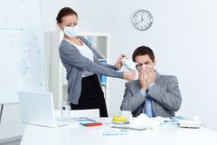 Protective measures. Image of businessman sneezing while his partner in mask offering him to put on one in office Royalty Free Stock Image