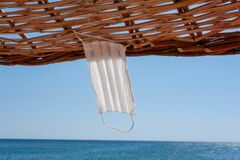 Free Protective Medical Mask Hanging On A Straw Sunshade On The Beach. Royalty Free Stock Photography - 193886317