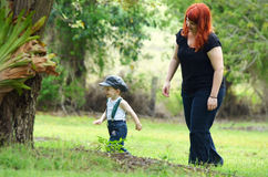 Protective mom walks behind her little toddler son boy in woods royalty free stock photography