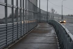 Protective noise barriers along the highway. A pedestrian road a royalty free stock image