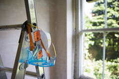 Protective safety goggles and dust mask hanging from step ladder in room beside window Royalty Free Stock Photography