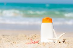 Protective sunscreen or sunblock and sunbath lotion in white plastic bottles on tropical beach, summer accessories in holiday,. Copy space. Summer Concept stock images