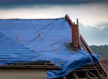 The tarp covers the roof. The protective tarpaulin on the roof flutters at the storm with rain. The tarp covers the roof of the old house in the reconstruction royalty free stock photos