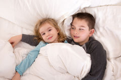 Protective young boy in bed with his little sister. Protective young boy is lying in bed with his little sister watching over her as she lies smiling up at the Royalty Free Stock Photos