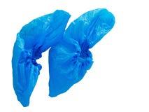 Protectores plásticos azules del zapato, cubiertas aisladas en el fondo blanco Higiene en las situaciones médicas etc No reutiliz imagen de archivo libre de regalías